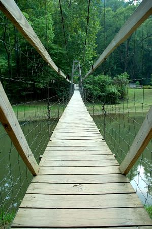 wobble: Foot Bridge - A wooden suspension footbridge spans the width of a river in Kentucky, USA.