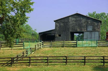 fenced in: Horse Barn - An old rustic barn for horses sits at the back of a fenced ranch in Kentucky, USA.