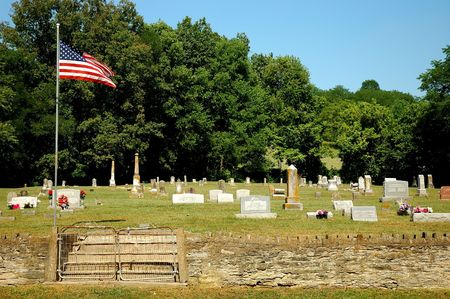 fenced in: Old Cemetery - The broken down stairs leading to the cemetary are fenced in. An American flag waves over the aged tombstones.