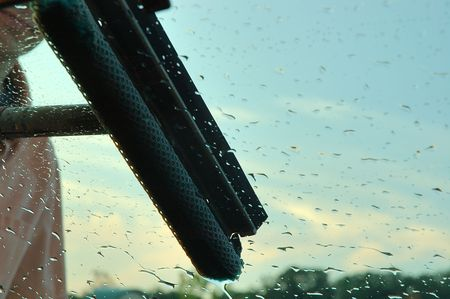 Window Washing - Image of a man washing the windshield of his car. Shows the sky in the background and water beads on the windshield. Stock Photo - 229059