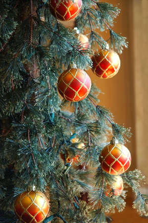 Christmas Tree - Red and gold glittery ornaments hang on the branches of a Christmas tree. Stock Photo