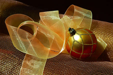 netting: Holiday Decorations - Decorative gossamer ribbon, a glittery tree ornament and gold netting fabric used for wrapping gifts and holiday decorating.