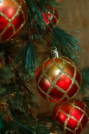 red glittery: Christmas Ornaments - Red and gold glittery ornaments adorn a Christmas tree.