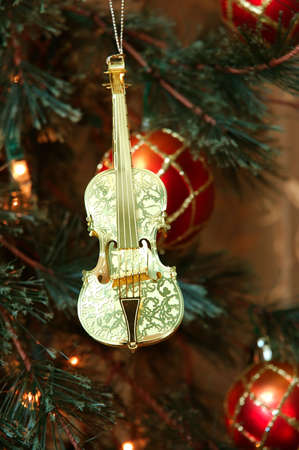 adorning: Violin - Shiny gold violin ornament hanging on a Christmas tree. Stock Photo