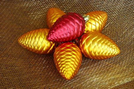 netting: Christmas Ornaments - Goud en rood pinecone vormige ornamenten op goud verrekeningsovereenkomsten weefsel. Stockfoto