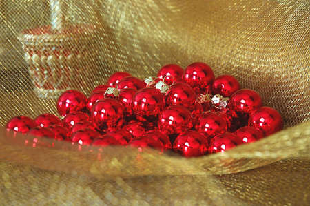 netting: Christmas Ornaments - shiny red ornament balls on gold netting fabric.