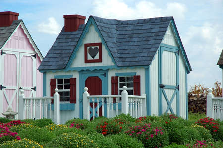 amish: Play House - An Amish built toy play house sits in front of mum bushes on a summer day.