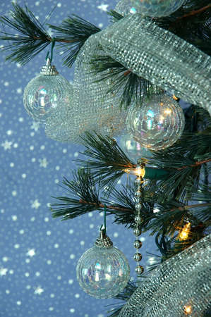 Iridescent ornaments, silver beads and glittery silver netting adorn a lighted Christmas tree.