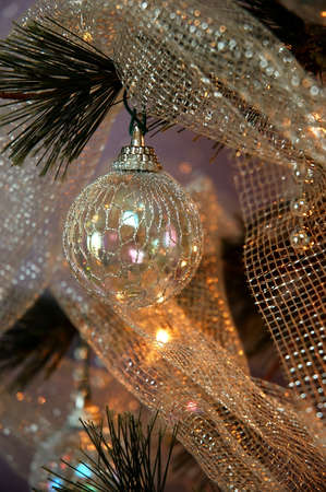 lighted: Iridescent ornaments, silver beads and glittery silver netting adorn a lighted Christmas tree.