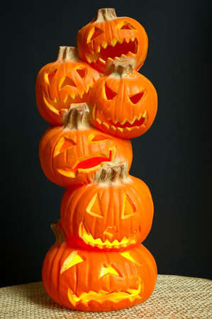 jacks: Jack O Lanterns - Halloween decoration - a stack of pumpkins that have been carved into lighted jack-o-lanterns sitting on a straw mat with black background. Stock Photo
