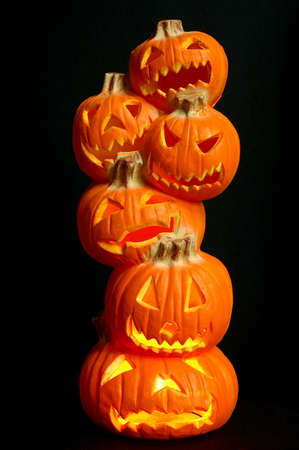 hallows: Jack O Lanterns - Halloween decoration - a stack of pumpkins that have been carved into lighted jack-o-lanterns with black background.
