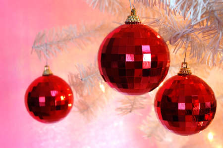 fake christmas tree: Christmas Tree Ornaments - Three red shiny ornaments hanging on the branch of a vintage white Christmas tree.