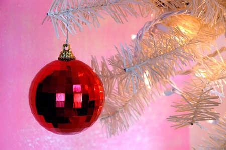 fake christmas tree: Vintage Christmas Tree - A red shiny ornament hanging on the branch of a vintage white Christmas tree.