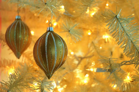 Vintage Christmas Tree - Two gold antique ornaments hanging on the branch of a vintage white Christmas tree.