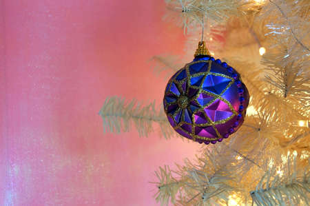 fake christmas tree: Vintage Christmas Tree - A purple and blue antique ornament hanging on the branch of a vintage white Christmas tree. Stock Photo