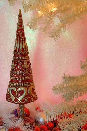 Vintage Christmas - A red and gold christmas tree stands next to the branches of a vintage white tree.