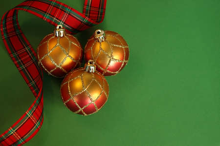 Christmas Ornaments - Plaid ribbon and red and gold glittery holiday ornaments on green cardstock background with room for copy.