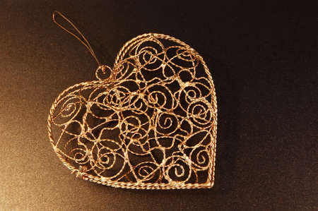 sparkly: Golden heart shaped ornament on bronze sparkly paper background.  Space for copy. Stock Photo