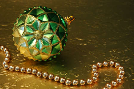 Green and gold ornament and gold beads on gold relfective, embossed paper.