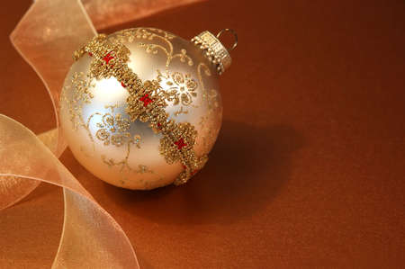 Vintage handmade Christmas ornament and gossamer gold ribbon over bronze paper.