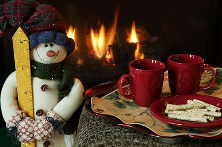 Cookies and hot drinks by the fireplace. Stock Photo