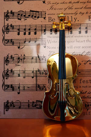 Golden violin standing in front of musical notes and text background. Stock Photo