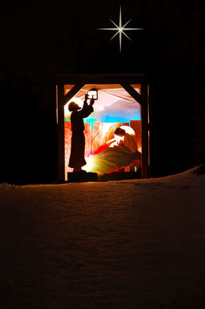 Nativity scene on a hill in the snow.  Joseph of Nazareth lights the lantern and Mary tends to her , Jesus.