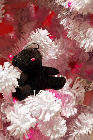 flocking: A snow covered black toy bear sits on the branch of a white flocked christmas tree. Stock Photo