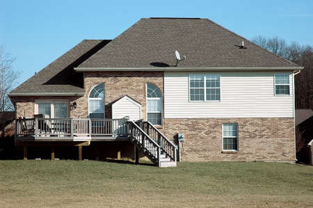 Back yard of a two story brick and vinyl house showing the deck.