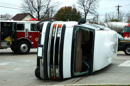 A van rolled on its side in an accident at an intersection with rescue emergency vehicles parked behind it.