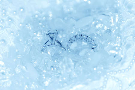 Something borrowed, something blue background.  Diamond wedding rings on icy blue pearls, crystals and lace. Stock Photo