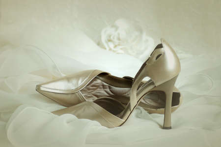 Soft focus vignette of wedding shoes resting on the brides veil. Stock Photo
