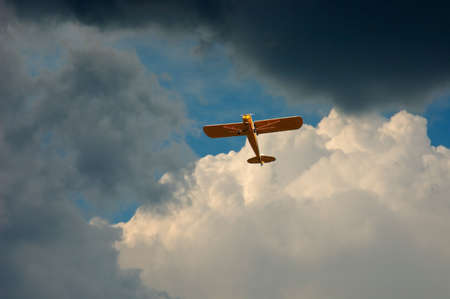 A piper airplane appears through the hole in the clouds on a stormy day. Stock Photo - 367661