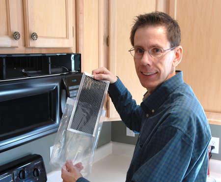zastąpić: Człowiek pokazano filtr zastąpi on jak jego naprawy mikrofalowa w kuchni z nowoczesnego domu.