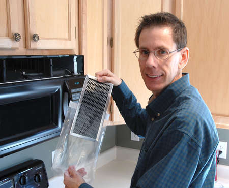 Man showing a filter he will replace as he repairs his microwave in the kitchen of a modern home.