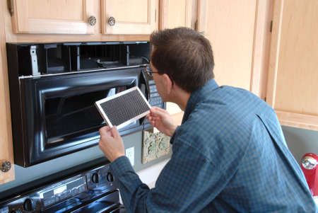 394564: Man replacing the filter in a microwave in the kitchen of a modern home.
