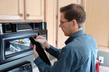 Man cleaning up after replacing the filter in a microwave in the kitchen of a modern home. photo