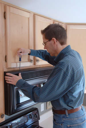 Man using a screwdriver to repair his microwave in the kitchen of a modern home. Stock Photo