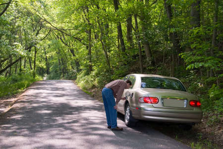 A man looking into his gas tank.  He's lost, on a country road and has run out of gasoline in his car. Stock Photo - 394597