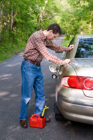 cranky: Upset man on a country road, staring at the empty gas tank of his car with a gas can at his feet. Stock Photo