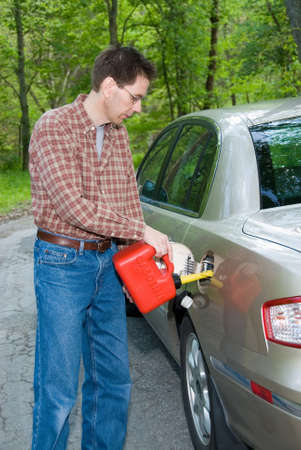 gas can: A man pouring gasoline into the tank of his car from a red gas can while stranded on a wooded country road. Stock Photo