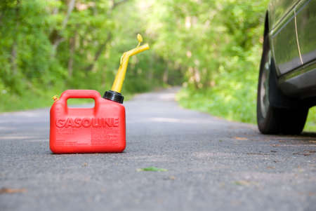 A red plastic gas can sitting in the middle of a country road next to a car. Stock Photo - 394610