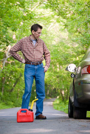 Upset man on a country road, staring at a gas can sitting on the road next to his car.  Focus is on the gas can. Stock Photo - 394604