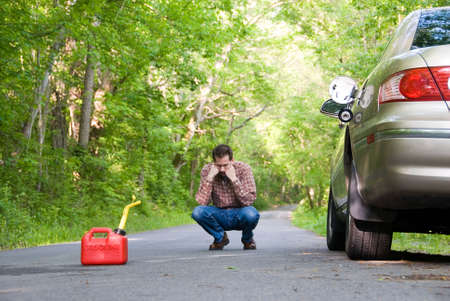 cranky: Upset man on a country road, staring at a gas can sitting on the road next to his car.  Focus is on the gas can.