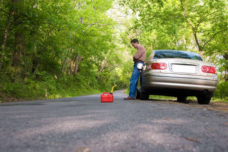 Upset man stranded on a country road, with a gas can at his feet. Stock Photo - 394621