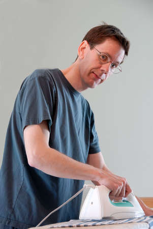 A man doing housework and ironing his clothes. photo