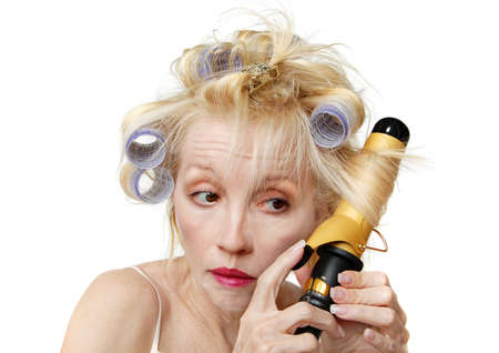bad hair day: Curler Woman - A blonde woman with lavender curlers in her hair, using a curling iron.  Bad hair day.