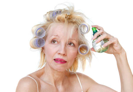 bouffant: A blonde woman with lavender curlers in her hair, spraying product onto her curls with an expression of worry on her face.  Bad hair day.