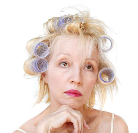 bad hair day: A blonde woman with lavender curlers in her hair, with an expression of hoping shell look better later.  Bad hair day. Stock Photo