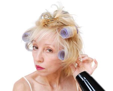 bad hair day: A blonde woman with lavender curlers in her hair, using a blow dryer.  Bad hair day.